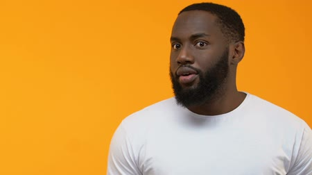 beard man : Excited black male pointing at bright background, place for your text, surprise Stock Footage