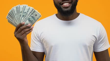 mevduat : Joyful african male pointing dollar bills in hand, financial success, investment Stok Video
