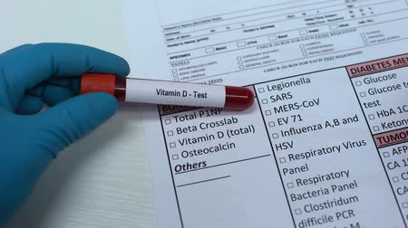 absorption : Vitamin D, doctor checking name in lab blank, showing blood sample in tube