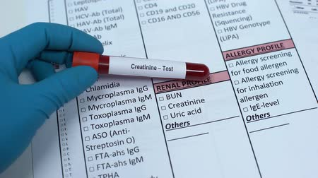 indicating : Creatinine, doctor checking name in lab blank, showing blood sample in tube