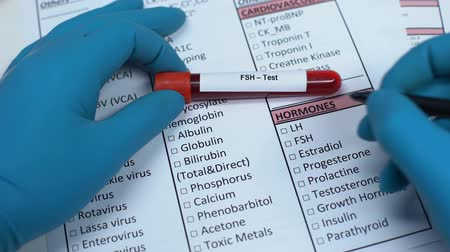 peptide : FSH, doctor checking hormone name in lab blank, showing blood sample in tube