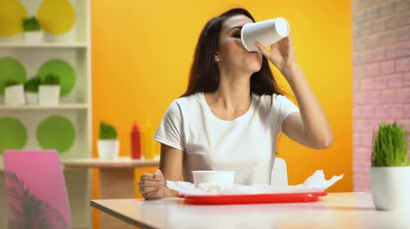 ízléses : Pretty woman drinking from paper glass in canteen, junk food overeating, snack Stock mozgókép