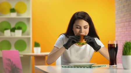 чизбургер : Young woman in black rubber gloves eating juicy hamburger sitting at cafe table