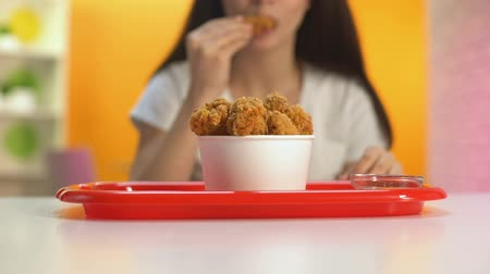 cantine : Female hand dipping fried chicken wings in tomato sauce, tasty unhealthy meal