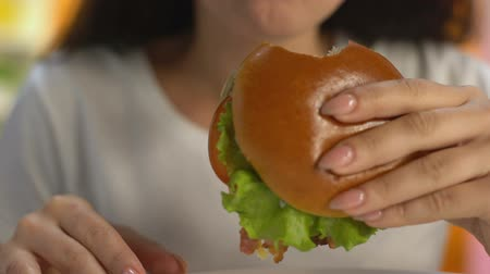 canteen : Female eating fat hamburger with tomato lettuce, fast food flavoring, calories Stock Footage