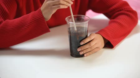 buzlu : Female customer tasting soft drink from plastic glass through straw, refreshment