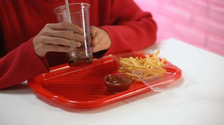 carbonated beverages : Female customer drinking carbonated water from plastic glass, unhealthy lunch