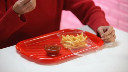 hasi : Woman eating french fries with ketchup feeling stomach pain, acid indigestion