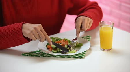 canteen : Lady eating vegetable salad with fork and knife and drinking fresh orange juice