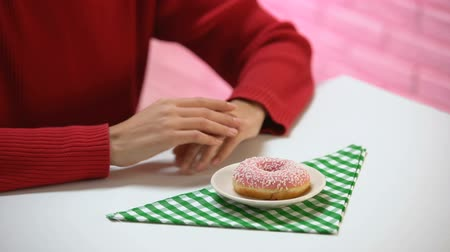hand sign : Woman showing no gesture refusing to eat sweet glazed donut, junk food rejection Stock Footage