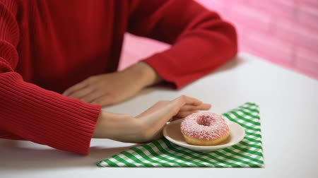 önlemek : Young female pushing away plate with glazed donut, refusing to eat sugar dessert