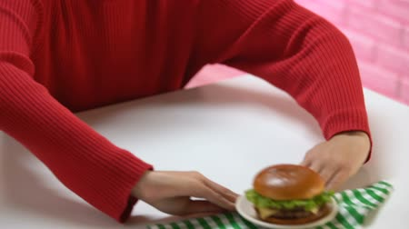 refusal to eat : Vegetarian female pushing away plate with burger, junk food calories, health