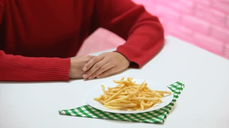 refusal to eat : Woman refusing to eat french-fried potatoes, fast food harm, cholesterol obesity