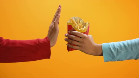 önlemek : Female hand showing stop gesture on yellow background, refusing eat french fries Stok Video