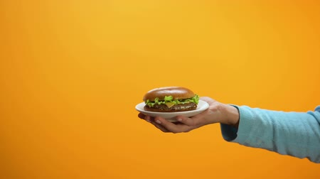 korlátozás : Female showing refuse gesture to burger on plate, fast food restriction, diet Stock mozgókép