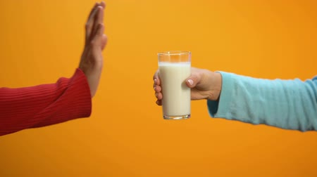 laktóz : Female refusing to drink milk showing stop gesture on bright background, health