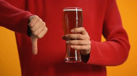 rejeitar : Woman holding glass of beer showing thumbs down, drunk driving danger, alcohol Stock Footage