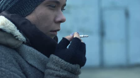 çaresiz : Homeless woman smoking on street feeling cold, poverty problems, drugs addiction
