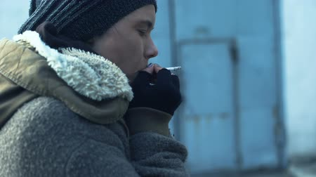tehetetlen : Addicted homeless woman taking cigarette from stranger and smoking feeling cold Stock mozgókép