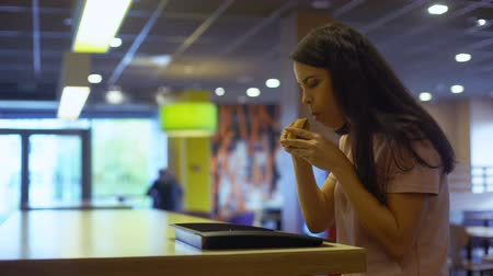 フライドポテト : Young lady eating burger sitting cafe table, junk food addiction, unhealthy meal 動画素材