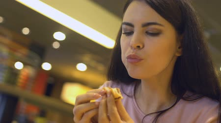 favori : Young brunette female chewing tasty sandwich, sitting in burger restaurant, meal
