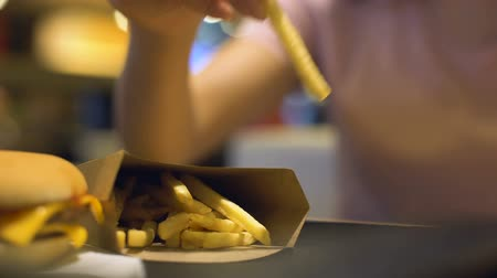 harmful : Lady hand taking french-fried potatoes from carton on table, cholesterol salt