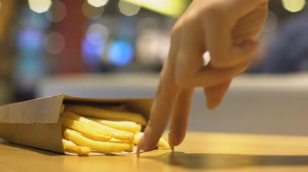 canteen : Lady fingers walking on table and taking crispy french fries from carton pack