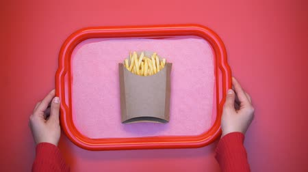 откорме : Female putting plastic tray with french fries on table, crunchy potato snack