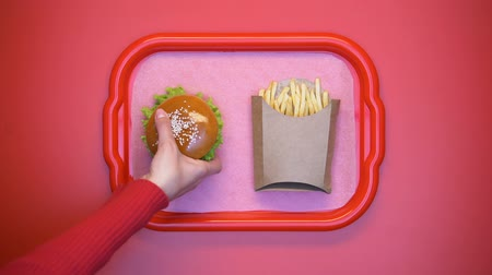engorda : Female hands taking hamburger and french fries from tray on bright background Stock Footage
