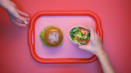 откорме : Hands taking hamburger and salad from plastic tray, student lunch in canteen
