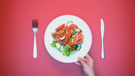столовые приборы : Woman hand putting plate with vegetable salad on table, vitaminized appetizer