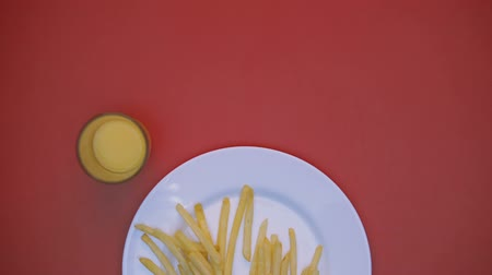 batatas fritas : Juice glass moving around plate, french fries disappearing, fast food dinner
