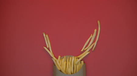 engorda : Crispy french fries making heart shape symbol on red background, fast food
