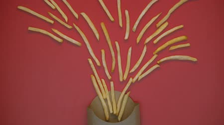 sarıcı : French-fried potatoes moving from carton box on red background, take away snack Stok Video