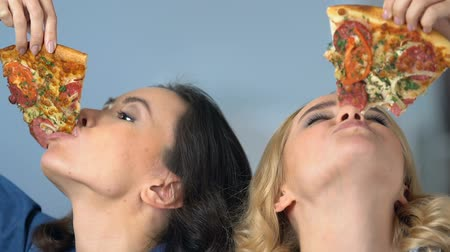 apetite : Beautiful roommates having fun eating fresh flavored pizza and smiling, party Vídeos