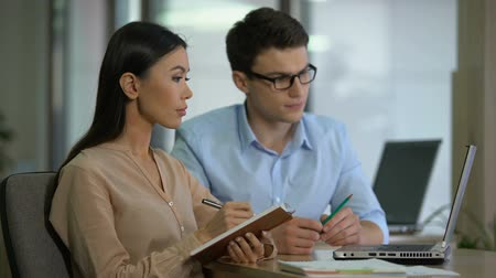 use laptop : Experienced male employee teaching new colleague, showing how to use application Stock Footage