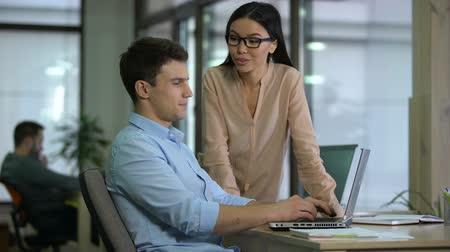 diligence : Business lady checking work of male trainee, praising diligence and perseverance Stock Footage