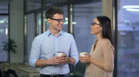 corporate affairs : Couple of teammates chatting during coffee break, friendly atmosphere in office Stock Footage