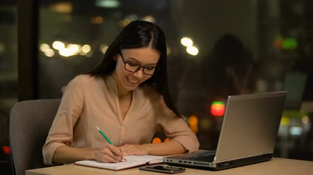 productiviteit : Young woman writing ideas into notebook, pondering plot of book, inspiration