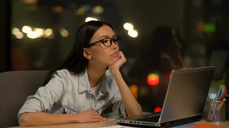 unloved : Young woman bored working on laptop in office, lacking motivation, unloved job
