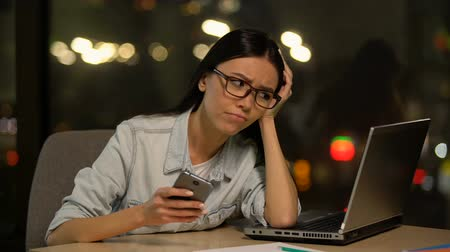 unloved : Young lady using cell phone at work, bored in office, shirking unloved job