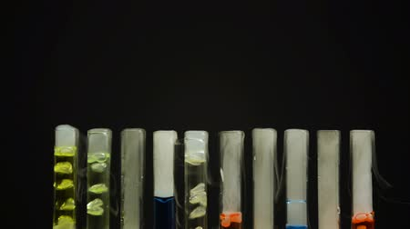 tlen : Multicolored narcotic substances in test tubes bubbling in darkness, smuggling.
