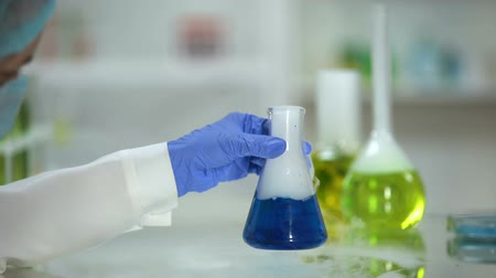 examinando : Lab assistant checking reaction in flask with blue substance emitting smoke