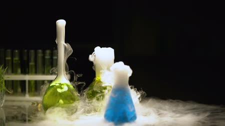 farmacologia : Multicolored substances in flasks bubbling and emitting smoke in darkness, test