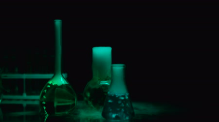 produtos químicos : Laboratory flasks with chemical liquids emitting smoke under blue blinking light