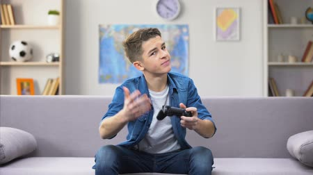 extremely : Teenage boy playing video game, strong emotional reaction, awkward age Stock Footage