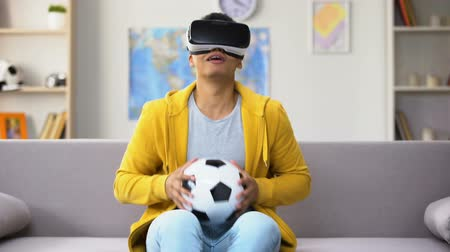 вратарь : Young Afro-American y in VR headset saving goal, pretending to be goalkeeper