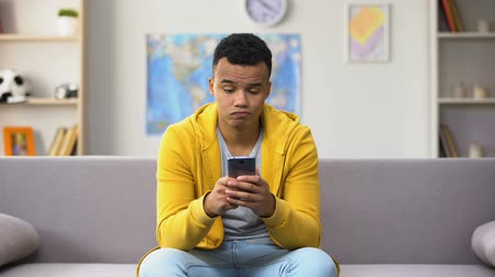 imitação : Bored black teenage guy scrolling smartphone, unhappy with search results
