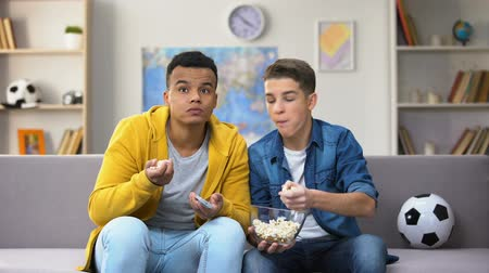 snoepen : Anxious teenage friends watching football match on TV and eating popcorn leisure Stockvideo