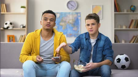 favori : Multiracial male teen friends discussing football match eating popcorn, leisure